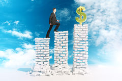 Financial growth concept. Financial growth and risk concept with young businessman in suit climbing abstract white brick ladder with golden dollar sign on top Royalty Free Stock Photography