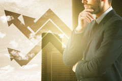 Financial growth concept. Side portrait of bearded young businessman with upward arrows on city background with sunlight. Financial growth concept Royalty Free Stock Image