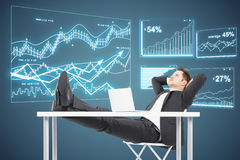 Financial growth concept. Side view of relaxing businessman looking at abstract digital business charts on grey background. Financial growth concept Royalty Free Stock Photo
