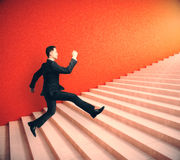 Financial growth concept. Side view of young businessman in suit running up red stairs. Financial growth concept. 3D Rendering Royalty Free Stock Photo