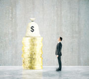 Financial growth man looking. Financial growth concept with businessman looking at money bag on top of golden coin stack in concrete room. 3D Rendering Royalty Free Stock Images