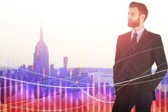 Financial growth and stock concept. Portrait of attractive young european businessman standing on abstract city background with forex chart. Financial growth and royalty free stock photo