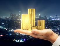 Financial growth and success concept. Hand holding pile of golden coins on city background. Financial growth and success concept. 3D Rendering Royalty Free Stock Photo