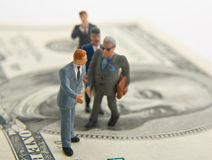 Financial Guidance. Miniature businessman guiding other miniatures on a hundred dollar bill Royalty Free Stock Image