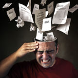 Financial Headache. Bills and financial papers coming out of a mans head with pain expression Stock Photo