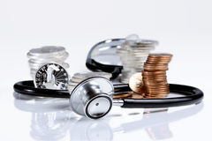 Financial health. Stethoscope weaving around stack of silver and gold coins Stock Photos
