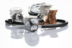 Financial health. Stethoscope weaving around stack of silver and gold coins Royalty Free Stock Photography