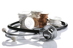 Financial health. Stethoscope weaving around stack of silver and gold coins Royalty Free Stock Image