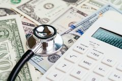 Financial health check, tax or medical and health care expense concept, stethoscope put on FED federal reserve emblem on US dollar. Banknotes with white royalty free stock photos