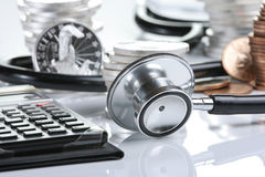 Financial health concept. Stethoscope weaving around stacks of silver and gold coins and calculator Royalty Free Stock Photos