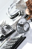 Financial health concept. Stethoscope weaving around stacks of silver and gold coins and calculator Royalty Free Stock Image