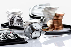 Financial health concept. Stethoscope weaving around stacks of silver and gold coins and calculator Royalty Free Stock Photography