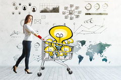 Financial idea concept. Side view of attractive young woman pushing trolley packed with light bulbs in concrete room with business charts on wall. Financial idea Stock Photography