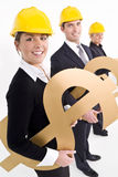Financial Industry. Conceptual studio shot of business executives holding various large golden currency symbols and wearing hard hats royalty free stock photography
