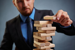 Financial instability. Businessman building tower with small wooden blocks Royalty Free Stock Photo
