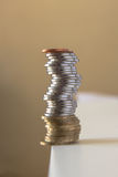 Financial instability. Pile of coins balancing on an edge risking to fall Royalty Free Stock Photography