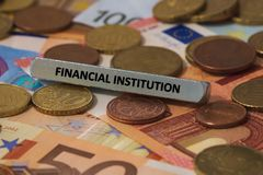 financial institution - the word was printed on a metal bar. the metal bar was placed on several banknotes stock photos