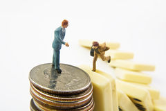 Financial Landing. Miniature man standing on quarters offering help to a miniature man running on falling dominoes Royalty Free Stock Image