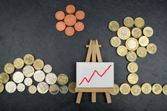 Financial Landscape UK. A simple landscape of Sterling coins with an easel depicting a rising chart Royalty Free Stock Images