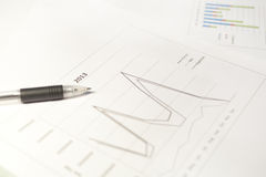 Line Chart. A financial line graph and a pen Royalty Free Stock Photos