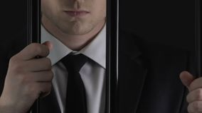 Financial manager hands holding prison bars, white collar crime, tax evasion. Stock footage stock video footage