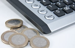 Financial market. A calculator with buttons tax - and plus together with coins in the front Stock Photos