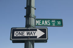 Financial Means One Way Money Sign. Means street sign above a one-way street sign pointing in the same direction against a blue sky stock images