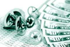 Financial Mechanism. Closeup of gears and dollar bank notes on paper list with digits Stock Photo