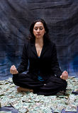 Financial meditation. Rich woman meditating while sitting in money isolated on a dark background royalty free stock photo