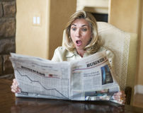 Financial meltdown in the newspaper. Mature woman reading the financial news Royalty Free Stock Images