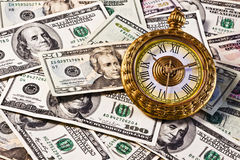 Financial Money Watch. The large pocket watch is sitting on top of the money. Possible application for financial planning Stock Images