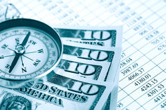 Financial Navigation. Dollar rate. Closeup of compass and dollar bank notes on paper list with digits Stock Photos