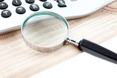 Financial newspaper with calculator and magnifier royalty free stock photography