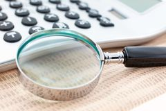 Financial newspaper with calculator and magnifier Stock Photo