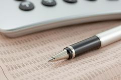 Financial newspaper with calculator and pen Stock Photo