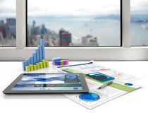 Financial office. Tablet and financial graphs on a white desk Royalty Free Stock Image