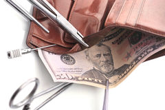 Financial operations. Surgical tools, purse and money Royalty Free Stock Image