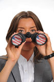 Financial outlook. Young corporate woman with binoculars reflecting American flag, Wall Street and NY Stock Exchange Royalty Free Stock Photo