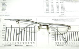 Financial paper, graphs, spectacles. Stock Photography