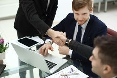Financial partners handshakes over a Desk in the office.  stock image