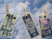 Financial Planning. Banknotes from around the world hanging on a clothesline against a bright sky Stock Images