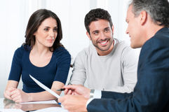 Financial planning consultation. Financial consultant presents bank investments to a young couple Stock Photos