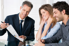 Financial planning consultation. Happy young couple discussing with a financial agent their new investment Stock Image