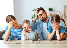 Financial planning   family mother father and children with piggy Bank bankrupt at home royalty free stock photos