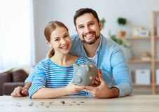 Financial planning happy family couple with piggy Bank at home royalty free stock images
