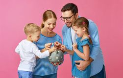 Financial planning happy family mother father and children with piggy Bank on pink stock photography