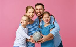 Financial planning happy family mother father and children with piggy Bank on pink stock images