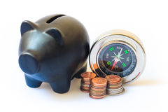 Financial planning at home, home finances plans idea with piggy bank, compass and coins. Royalty Free Stock Image