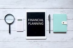 Financial planning. Top view of magnifying glass,calculator,pen,notebook and tablet computer written with & x27;FINANCIAL PLANNING& x27; on white wooden Royalty Free Stock Photos