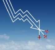 Financial Plunge. Business concept as a group of air show acrobatic jet airplanes creating a smoke pattern shaped as a finance diagram in descent and profit Royalty Free Stock Photography